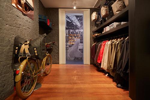 Kläder från kollektionen John Boultbee hänger prydligt uppradade i Brooks Englands konceptbutik, B1866.